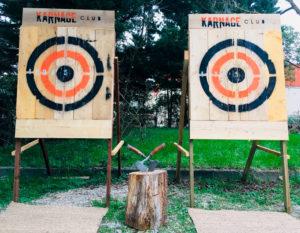 Cibles movibles pour le lancer de haches du Karnage Club, derrière deux haches plantées dans un rondin en bois