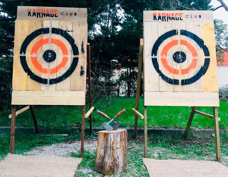 Cibles mobiles pour le lancer de haches du Karnage Club, derrière deux haches plantées dans un rondin en bois