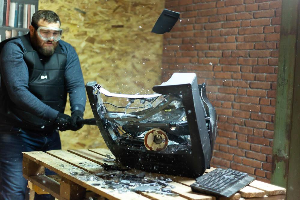 Homme explosant une télévision à coups de batte de baseball dans une rage room du Karnage Club